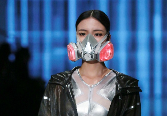 A model wearing a mask presents a creation at the QIAODAN Yin Peng Sports Wear Collection show during China Fashion Week in Beijing